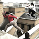 Photo of two traceurs using their parkour and freerunning skills against a city skyline
